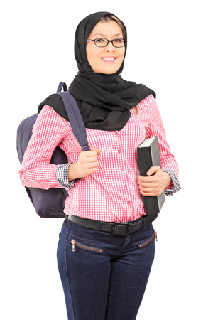 Female student with traditional Islamic veil holding book isolated on white background photo