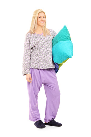 lady slipper: Full length portrait of a blond girl in pajamas holding a pillow isolated on white background Stock Photo