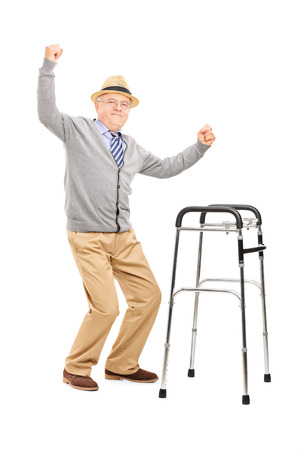 Full length portrait of an old man with a walker raising his hands isolated on white background