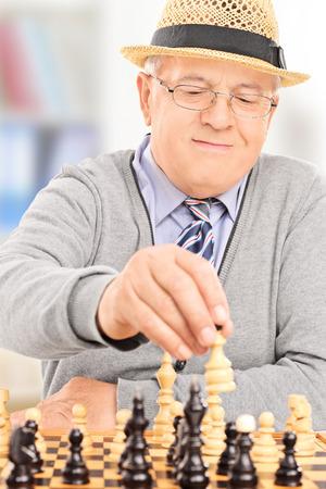 Senior gentleman playing chess indoors photo