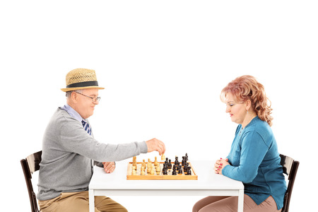 Mature couple playing chess seated at a table isolated on white background photo
