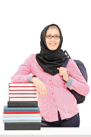 Religious female student leaning on a stack of books isolated on white background photo