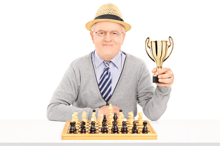 Senior chess player holding a trophy isolated on white background photo