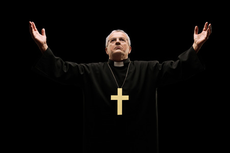 Mature priest praying to god isolated on black background