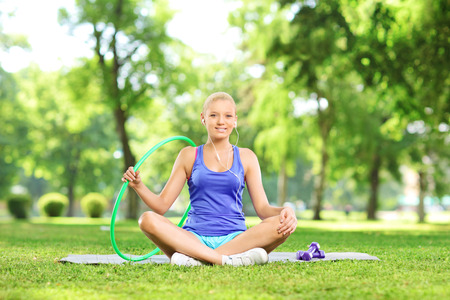 Young female fitness instructor sitting in park photo