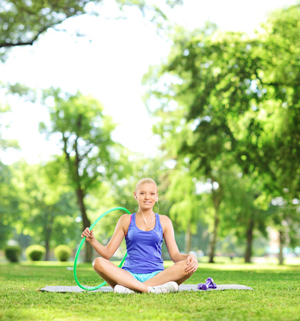 Female athlete sitting in park with exercising equipment shot with tilt and shift lens photo