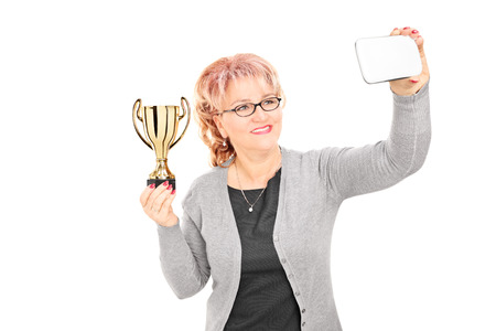 Mature woman holding trophy and taking a selfie isolated on white background photo