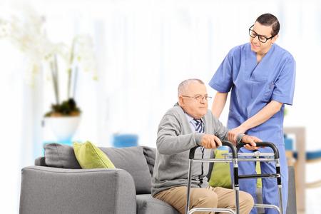 Mannelijke verpleegster helpt een oudere man op te staan in een verpleeghuis