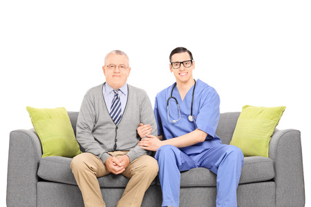 Young doctor and senior gentleman posing on sofa isolated on white background photo