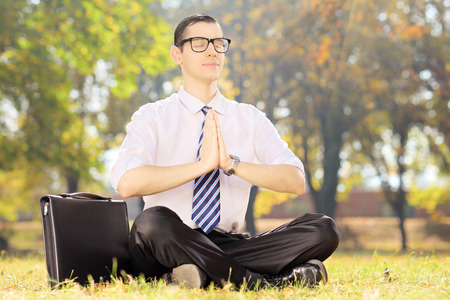 Businessperson with eyeglasses doing yoga exercise seated on a green grass in a park photo