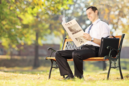 Young man seated on a wooden bench reading a newspaper in a park on a sunny day photo