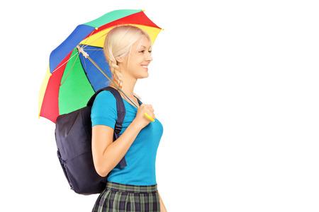 Blond female student walking with umbrella isolated on white background photo