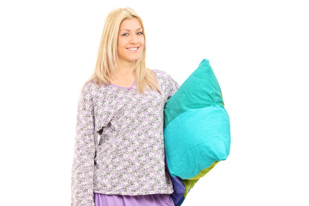 Blond girl in pajamas holding a pillow isolated on white background photo