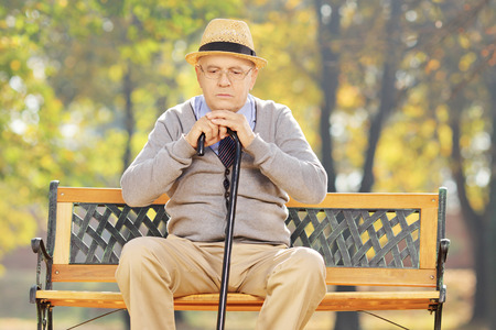 dissappointed: Thoughtful senior man with a cane sitting on bench in a park