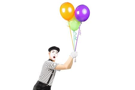 pantomima: Mimo joven que sostiene globos y volando aisladas sobre fondo blanco