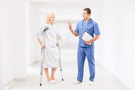 Female patient in gown with crutches and medical doctor during a conversation in clinical corridor photo