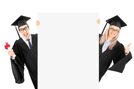 Young man in graduation gown holding diploma and a girl giving thumb up behind blank panel isolated on white background photo