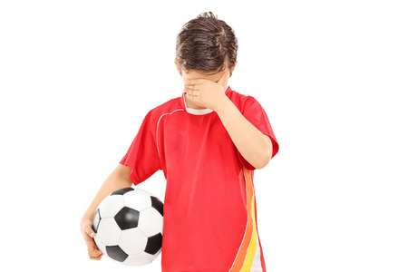 Sad boy with soccer ball isolated on white background photo