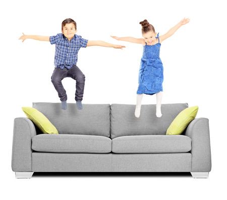 Brother and sister jumping on sofa isolated on white background