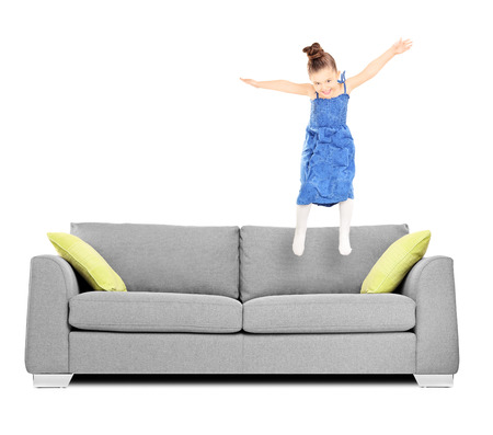 Happy female kid jumping on couch isolated on white background shot with tilt and shift lens photo