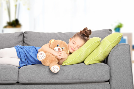 Little girl sleeping on couch with teddy bear indoors Stock Photo