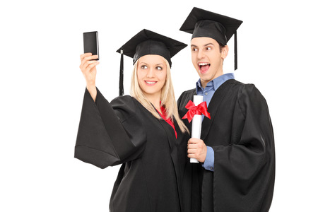Male and female graduate students taking a selfie isolated on white background photo