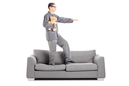 Man in pajamas sleepwalking on sofa isolated on white background