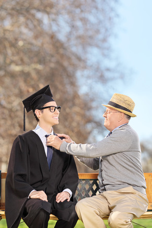 College student and his proud father sitting on wooden bench in park photo