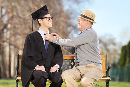 Father preparing his son for graduation seated on wooden bench in park photo