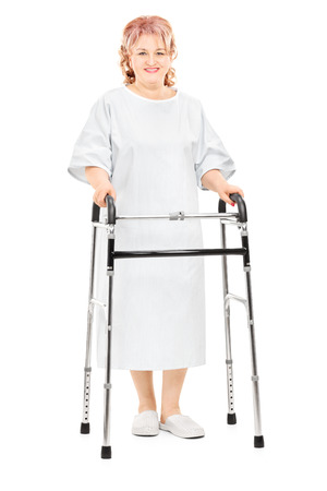 Full length portrait of a female patient walking with walker isolated on white background Stock Photo - 26999054
