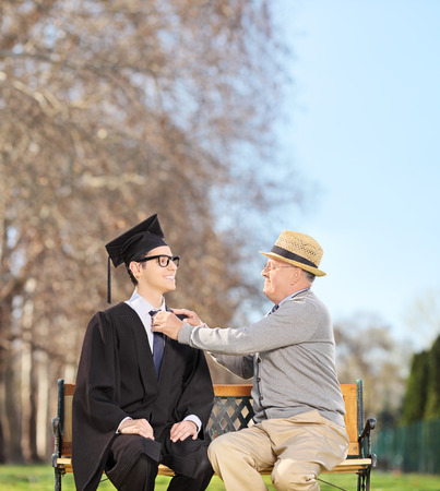 Graduate student and his proud father sitting on a wooden bench in park shot with tilt and shift lens photo