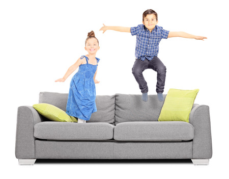 Boy and a girl jumping on the couch isolated on white background photo