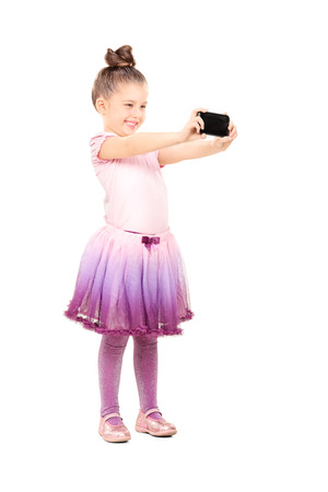 Full length portrait of little ballerina taking a selfie isolated on white background photo
