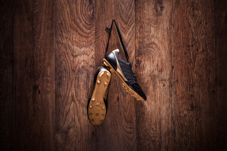 Pair of football boots hanging on a wooden wall