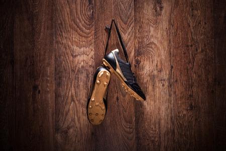 ropa colgada: Par de botas de fútbol que cuelga en una pared de madera