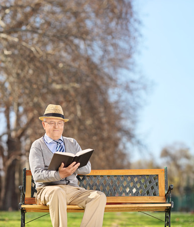 Senior sitting on bench and reading a book in park shot with tilt and shift lens photo