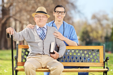 Healthcare professional posing with a senior man in park photo