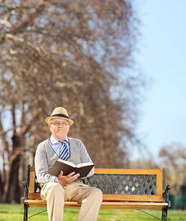 old man sitting: Senior gentleman reading a book in park and looking at the camera shot with tilt and shift lens