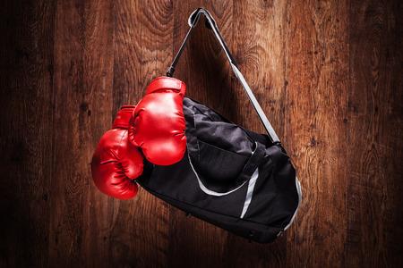 Sporttas en bokshandschoenen opknoping op een houten wand Stockfoto - 27078347