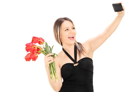 Girl holding flowers and taking a selfie isolated on white background photo