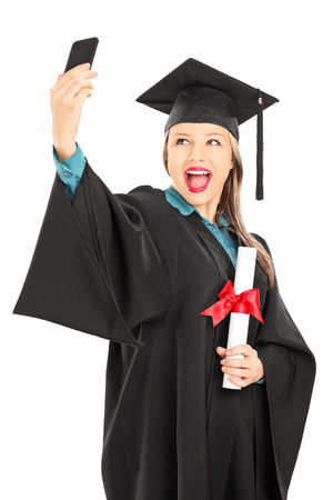 Female college graduate holding a diploma and taking selfie isolated on white background photo