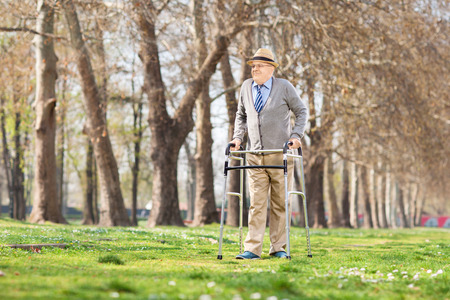 recovering: Senior gentleman walking with walker in park