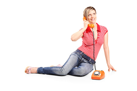 Young girl talking on a vintage phone isolated on white background photo