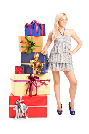sexy birthday: Full length portrait of an attractive girl standing next to a stack of gifts isolated on white background