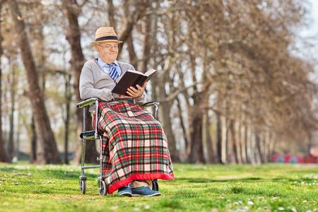 Elderly gentleman reading a book outdoors photo