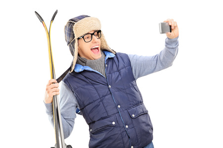 Man in winter clothes taking a selfie with skis isolated on white background photo