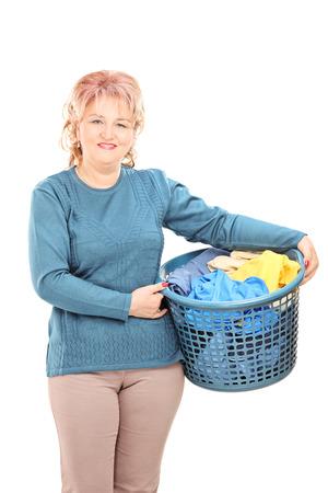 Mature woman holding a laundry basket isolated on white background photo