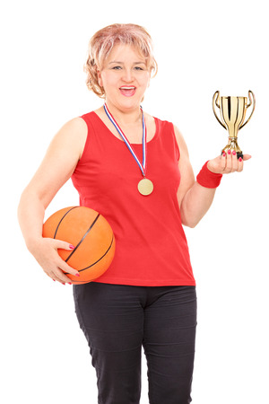 Mature woman holding trophy and a basketball isolated on white background photo