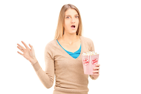 Shocked woman holding a box of popcorn isolated on white background photo