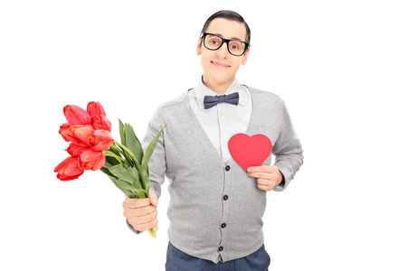 Thoughtful guy holding a red heart and flowers isolated on white background photo